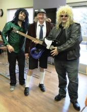 Three men with heavy metal outfits and wigs. One holding an electric guitar.